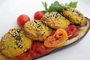 לביבות כרובית ללא שמן וללא גלוטן, מוגשות על סירת חציל אפויה בגריל ורוטב עגבניות שרי ולימונים