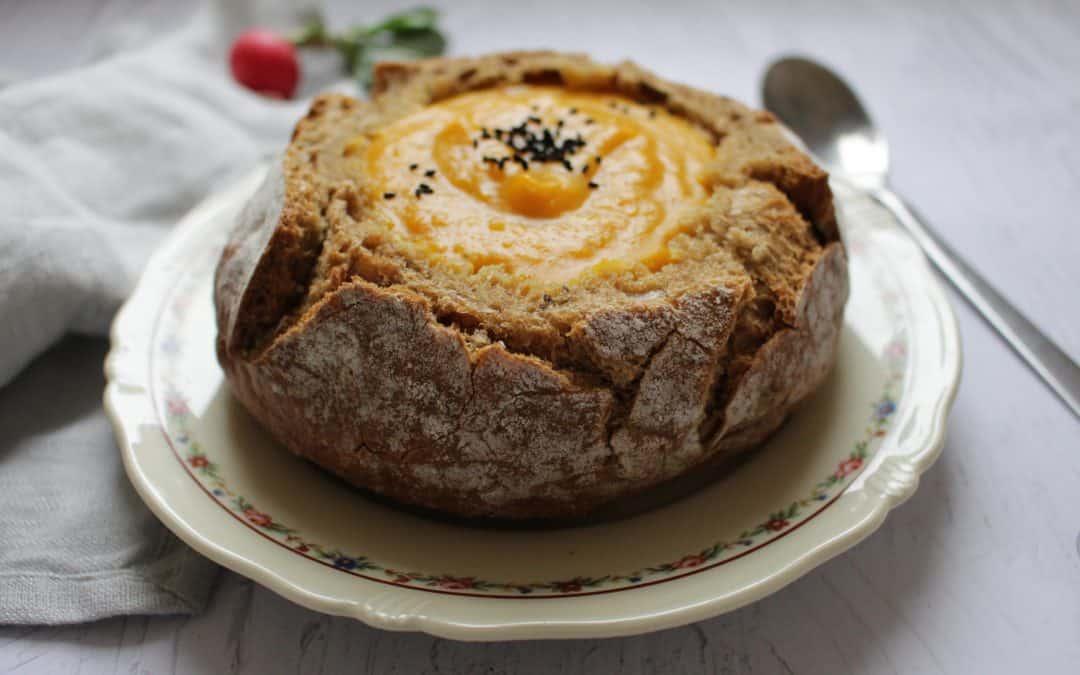 מרק כתום בקערית לחם מחמצת כוסמין מלא