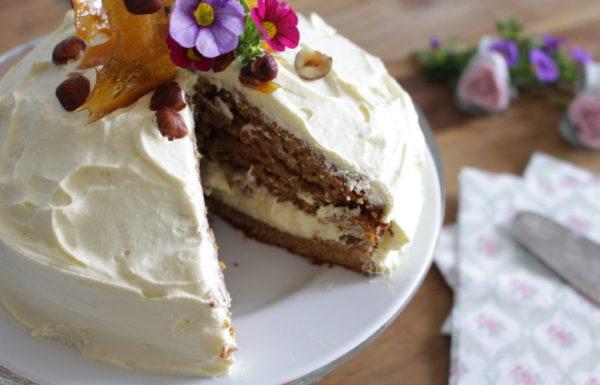 עוגת דבש תמרים משגעת, טבעונית, מעוטרת קרם ושברי קרמל ואגוזי לוז